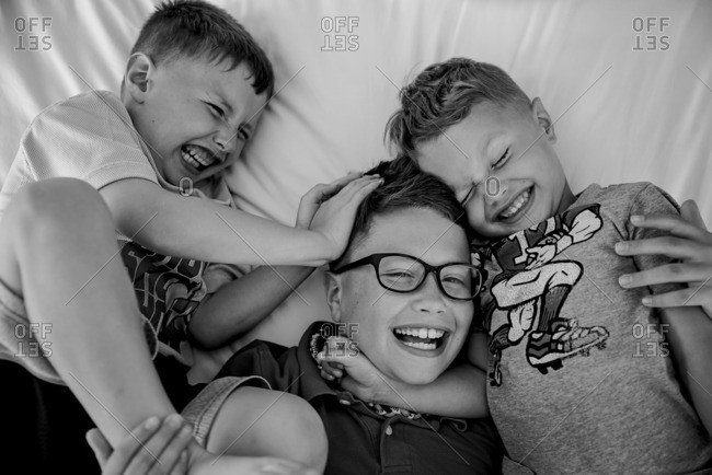 Three brothers wrestling on bed