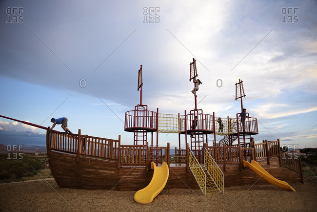 Kids climbing pirate ship shaped structure