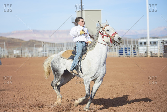 Boy riding horse in rodeo