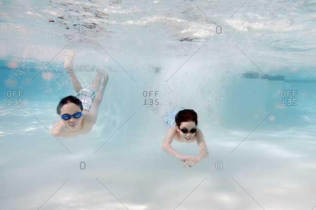 Boys swimming underwater in a swimming pool