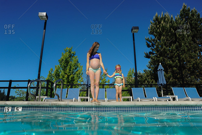 Pregnant mother standing pool side with her daughter