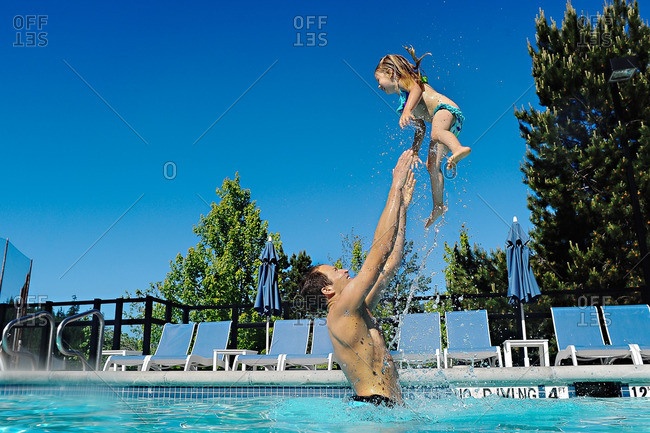 Father playing with his daughter in a swimming pool