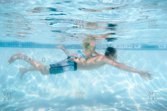 Daughter swimming on her father's back underwater in a swimming pool