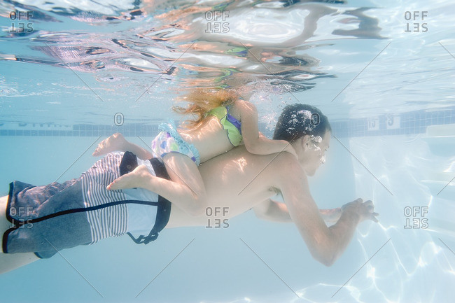 Daughter swimming on her father's back underwater