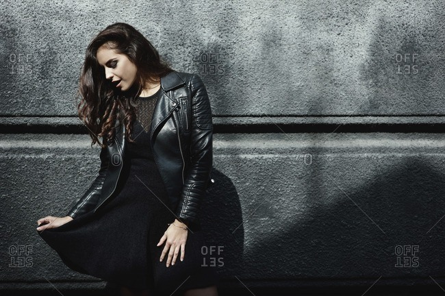 Young woman playfully posing in leather jacket against a concrete wall