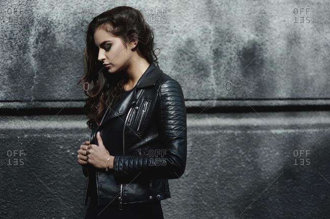 Young woman posing in leather jacket against a concrete wall