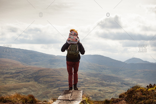 Man with girl on shoulders on mountain