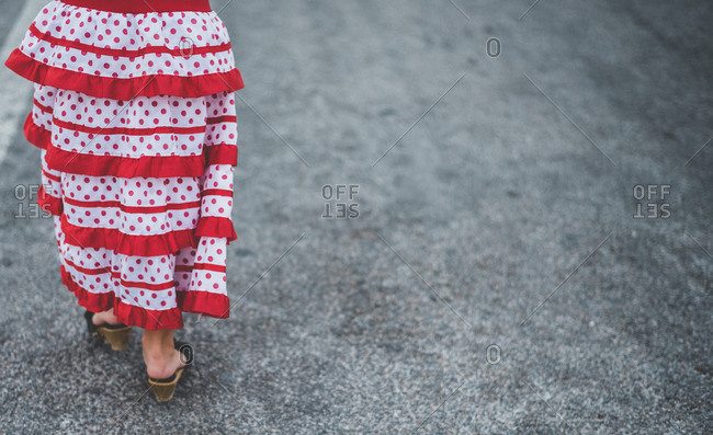 Woman wearing a colorful polka dot dress walking down a street alone