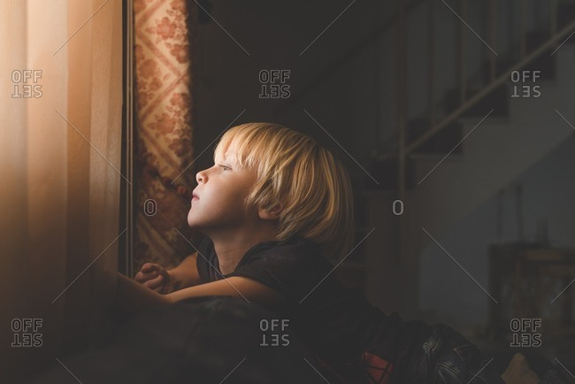 Boy sitting on a couch in  a dimly lit room looking out of the window