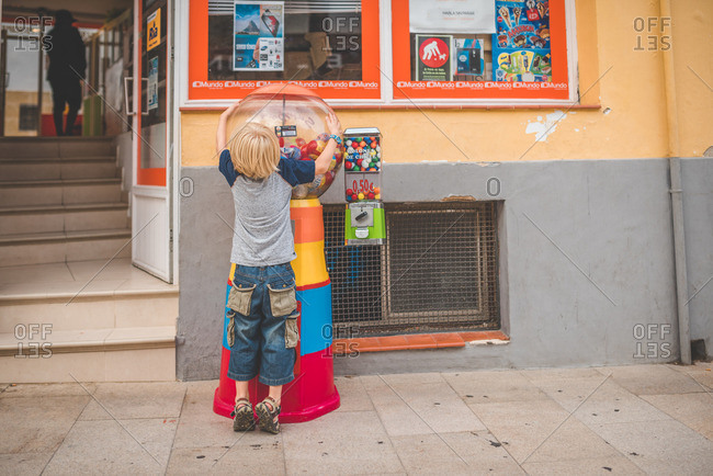 Spain - September 29, 2016: A boy stands near a bubblegum machine on a sidewalk in Spain