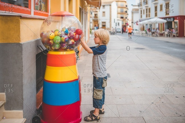 Spain - September 29, 2016: A boy stands near a bubblegum machine on a city sidewalk in Spain