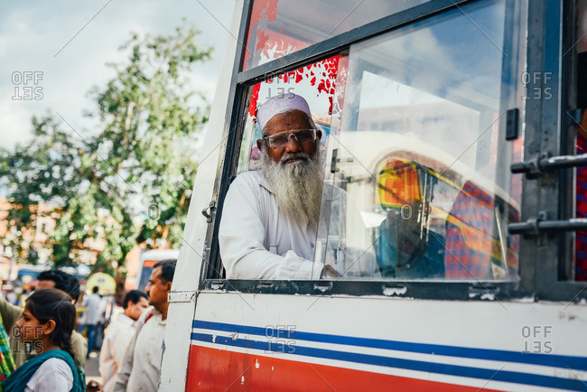 Jaipur, India - October 3, 2013: An old man waiting in a public bus in Jaipur, India