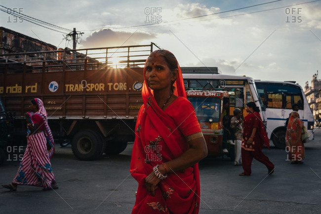 Jaipur, India - October 3, 2013: A woman with a colorful red sari walking in the street in Jaipur, India