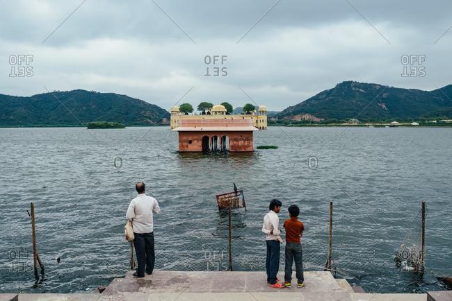 Jaipur, India - October 4, 2013: Three people standing at the edge of Sagar Lake in Jaipur, India
