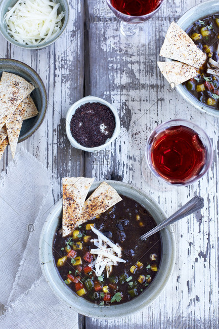 Bowls of black bean soup  with roasted peppers and cilantro served with red wine, cheese and ancho tortilla chips