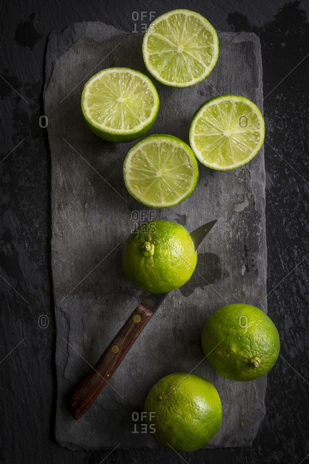 Whole and cut limes on black slate board with knife cutting one of the limes