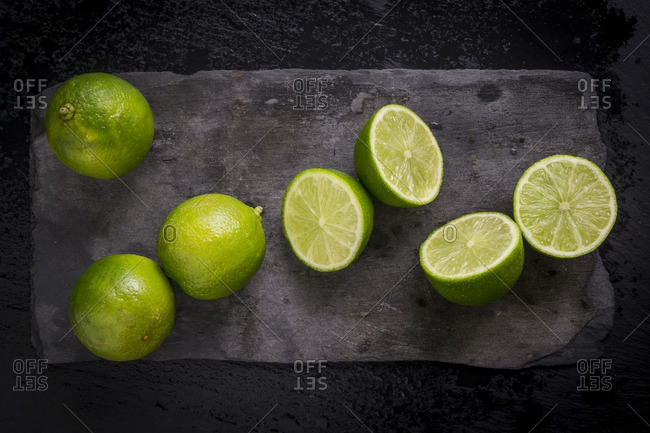 Whole and cut limes on black slate board