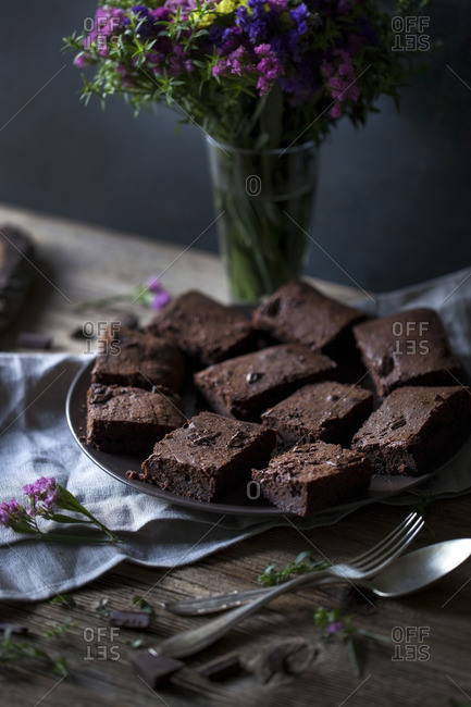 Dark chocolate coconut oil brownies on a rustic wooden table