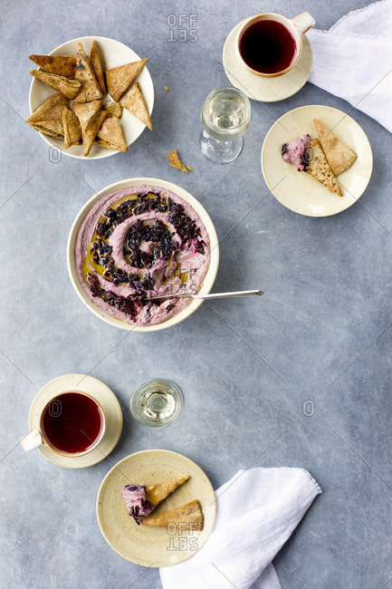 Hibiscus hummus topped with hibiscus flowers and olive oil served with pita chips and white wine