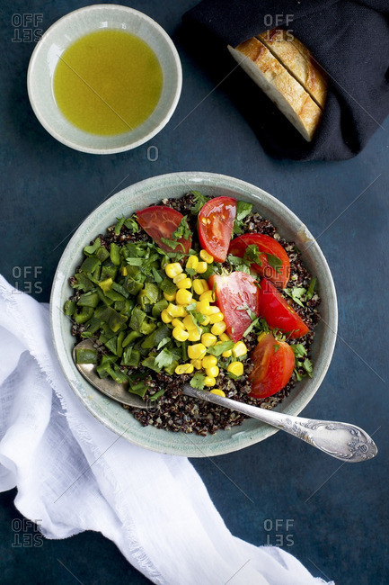 Roasted poblano quinoa topped with corn, tomatoes and cilantro and served with olive oil and bread