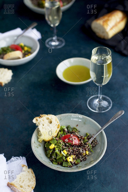 Roasted poblano quinoa served on plates with bread and wine