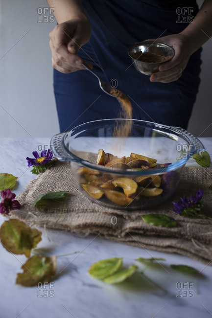 Woman sprinkling coconut sugar on sliced plums for a plum galette
