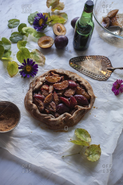 Baked plum galette on a baking paper and white marble table