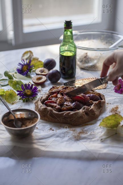 Woman slicing baked plum galette on a baking paper and white marble table