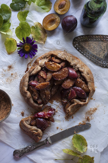 Baked plum galette on a baking paper with serving cut out