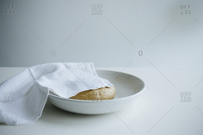Dough in a bowl partially covered on a white table