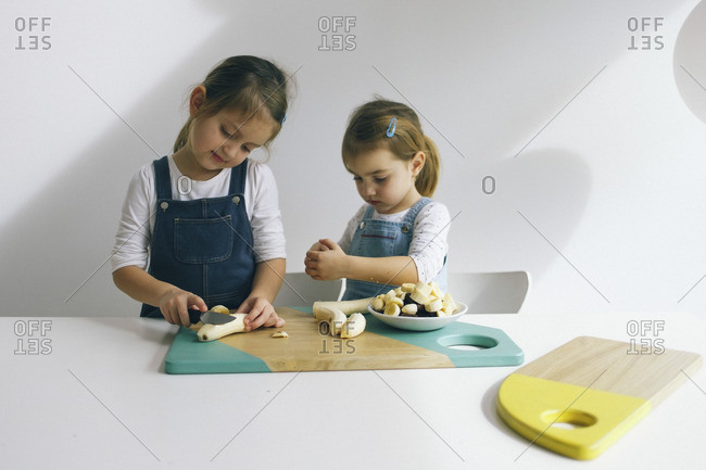 Two little girls chopping bananas on a wooden cutting board