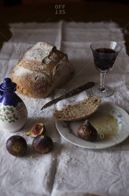 Rye bread, olive oil, sea salt, glass of red wine and fresh figs on a table