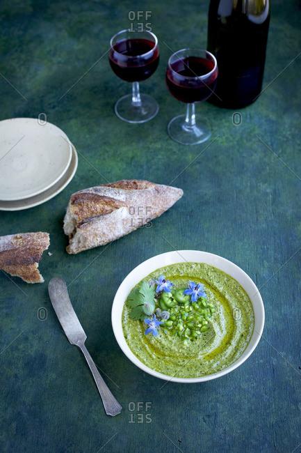 Roasted jalapeno cilantro pesto topped with jalapeno, cilantro and borage flowers with bread and wine
