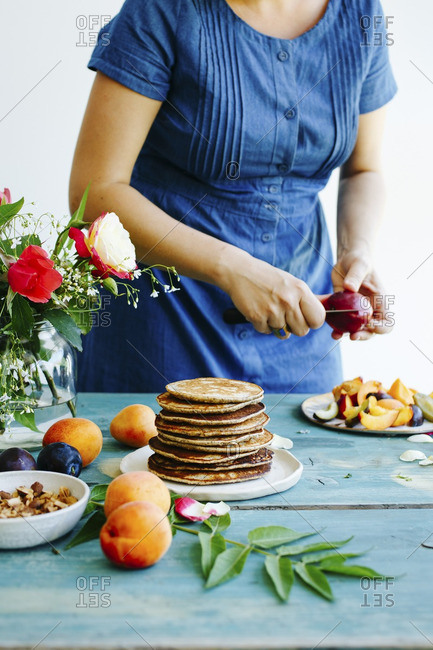 Pancakes on a wooden table and woman slicing fruit