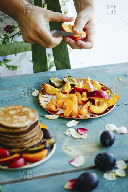Woman slicing peaches on a table with pancakes