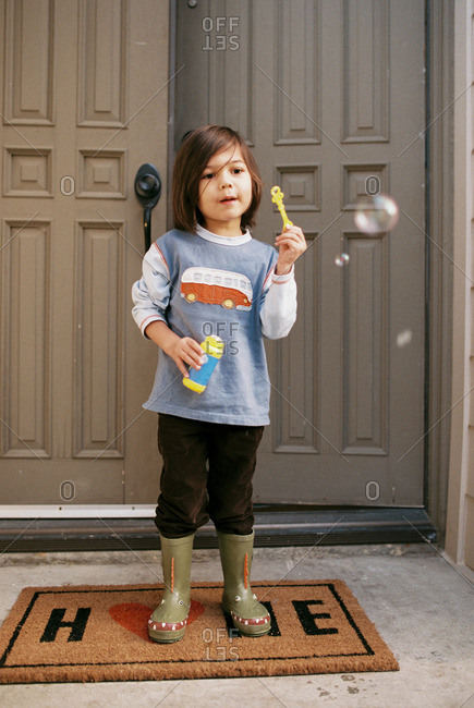 Boy blowing bubbles on front stoop