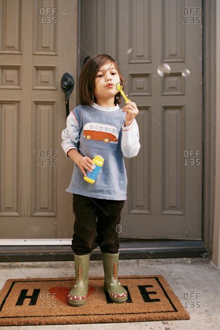 Little boy blowing bubbles on front stoop