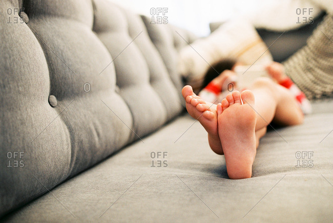 Close up of little boy's bare feet on a couch