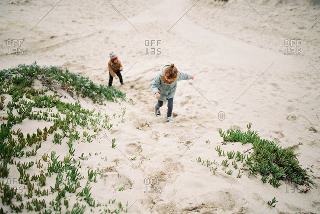 Children climbing up a sand hill