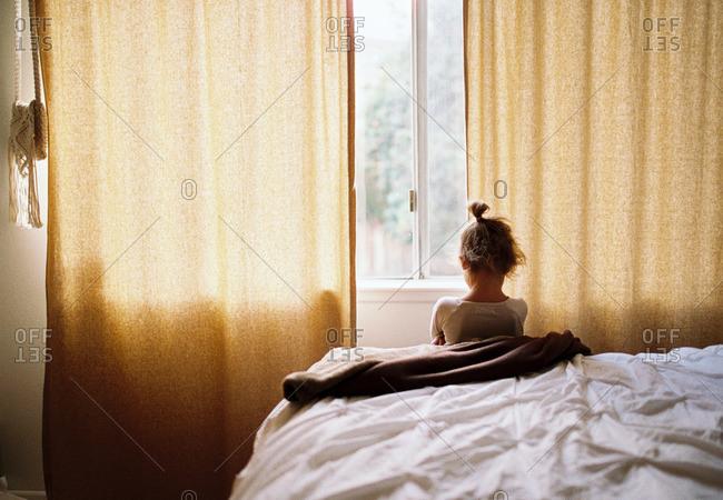 Little girl looking out hotel window