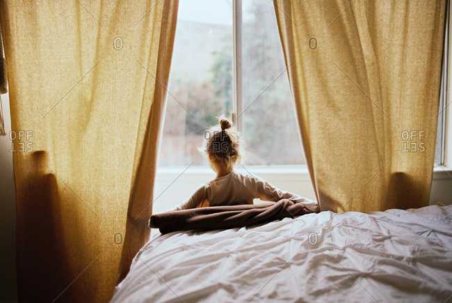 Girl opening drapes to look out hotel window