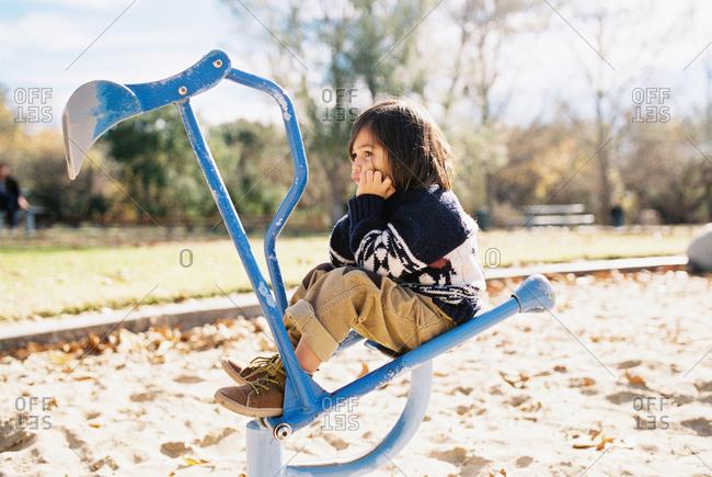 Bored little boy sitting on playground equipment