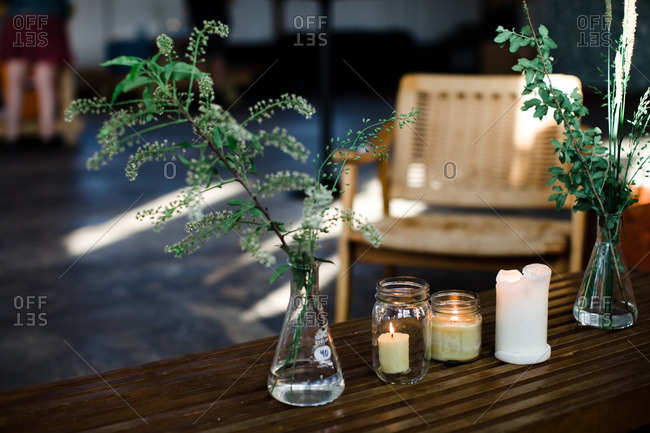 Plants in glass beakers beside lit candles