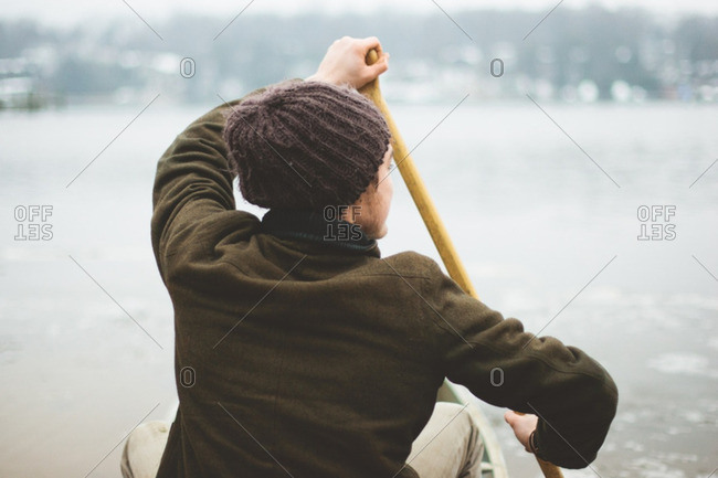 A man with a knit hat and coat paddling a canoe in winter