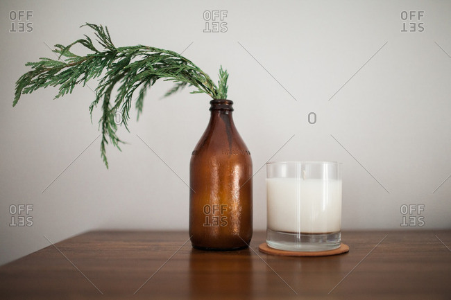Cedar branch in a brown jug beside a candle