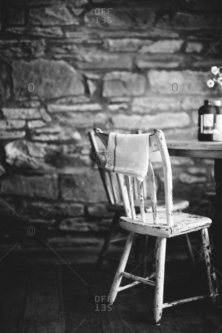 Old wooden chair at a dining room table in black and white