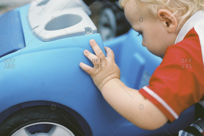 Toddler boy looking at his toy blue car