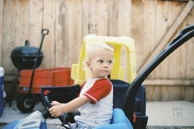 Toddler boy riding in a toy blue car and looking back