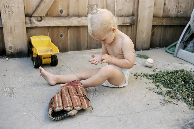Toddler boy sitting on ground beside baseball glove in backyard