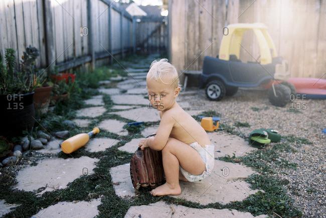 Toddler boy playing with baseball glove in backyard
